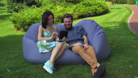 A young couple sitting in a chair ottoman park and viewing photos on the tablet Footage