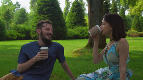 A young couple sits on the ground in the park and drink coffee Footage