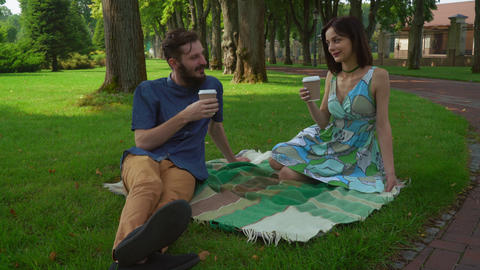 A young boy and girl talking and drinking coffee, sitting on the lawn in the par Footage