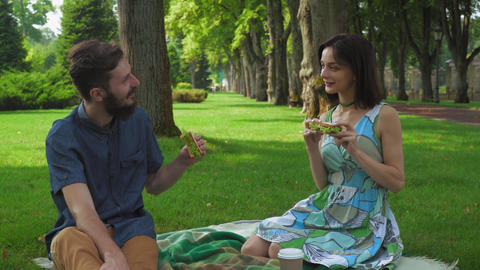 Young couple in summer picnic park to eat sandwiches, enjoying the flavor and sm Footage