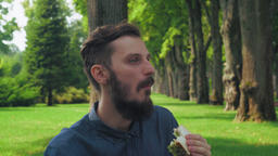 Man eats a sandwich with salad in the park. Enjoying the taste and closes his ey Footage