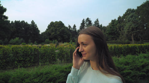 Young brunette girl slowly passes through the park and talking on the phone Footage
