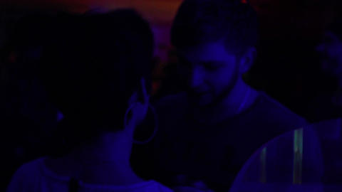 Guy in nightclub flirting and kissing girls, dancing to music on dance floor Footage