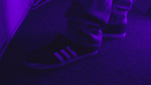 DJ tapping foot to the rhythm of music in nightclub. Sneakers close-up Live Action