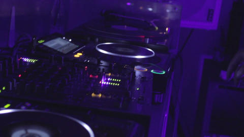 Dj controls the sound in nightclub hands do active moves on mixer and turntable Footage