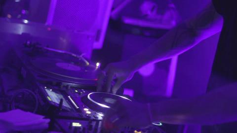 DJ tweaks turntable and mixer, controls music in nightclub Footage