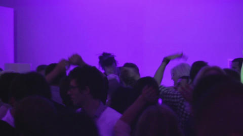Crowd in nightclub waving hands in the air, DJ playing, active camera movement Footage