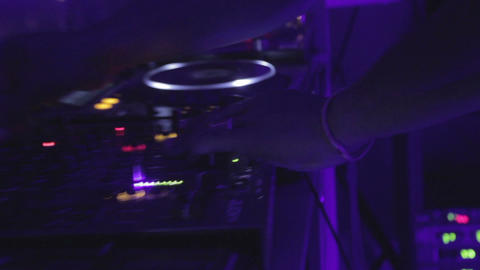 Afro dj plays set in nightclub, controls turntable and mixer. Wide and close-up Footage