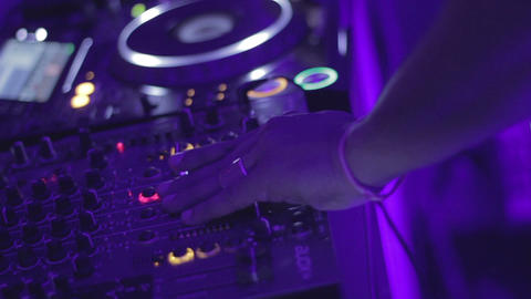 DJ with funny dreads playing music in nightclub. Controls sound mixer, turntable Live Action