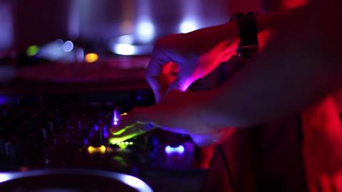 Female dj hands crossed tweaking mixer controls, playing music in nightclub Footage