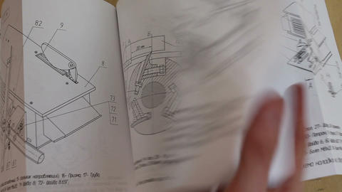 Paper sheets of technical manual, with text and charts Footage