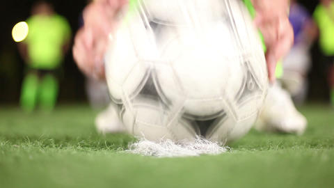 Soccer ball placed on penalty spot of green field by football player. Close up Footage