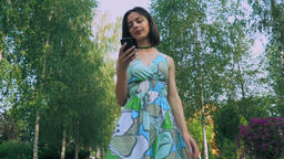 Young girl in a bright dress is in the park, reading a message on your phone and Live Action
