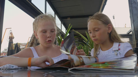 Two girls looking menu in outdoor summer cafe. Young girl teenagers talking and GIF