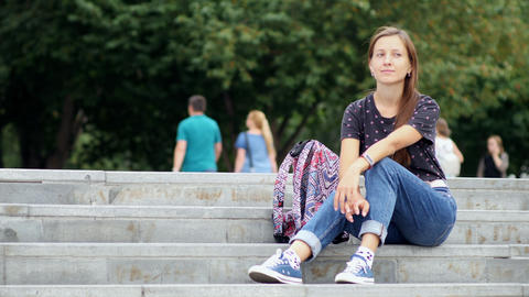 Woman sit on the stairs outside Live Action