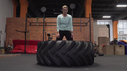 Fitness woman doing tire flips workout at gym Live Action