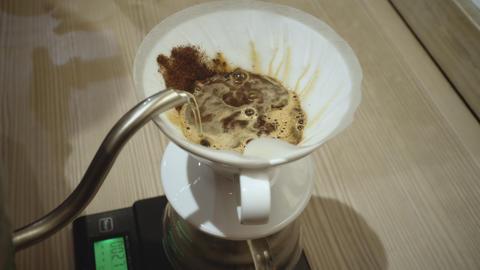 Barista making coffee using a funnel GIF