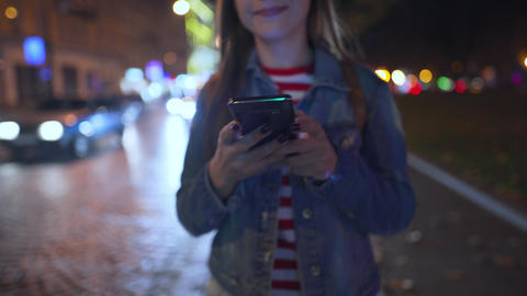 Woman uses a smartphone while walking through the streets of the evening city Footage