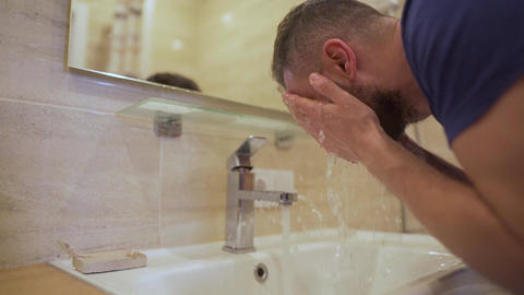 Morning hygiene. Man washes his face with clean water in the bathroom Live Action