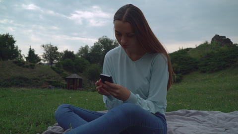 A young girl sitting on blankets on the lawn in the park and gaining a message o Footage