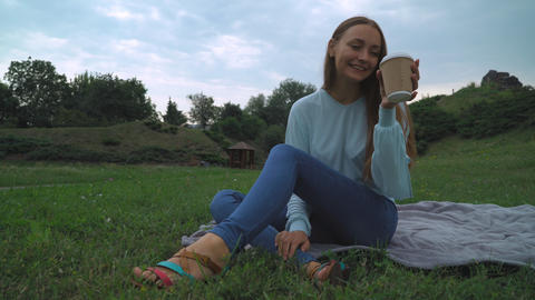 A young girl in a green blouse sitting on the lawn in the park, drinking a drink Live Action