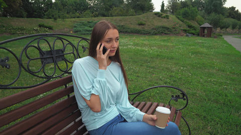 A young girl sits on a park bench holding a drink and talk on the phone Footage