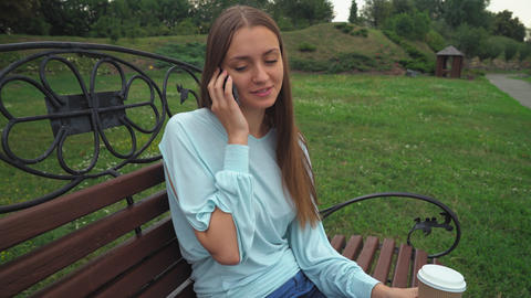 A young girl sits on a park bench, holding a drink and talking on the phone, smi Footage