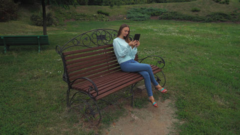 Young girl with long hair sitting on a park bench and holds the tablet, smiling Footage