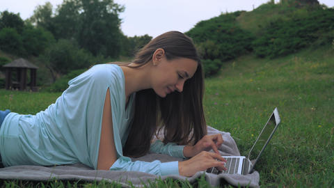 A young woman lies on lawn and gaining a message on the computer. Laughing, rejo Footage