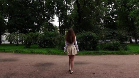 Young woman in short skirt and white blouse go on gravel path and turn around Archivo