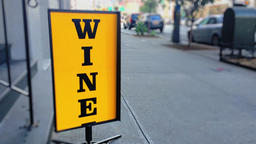 Spinning Wine Sign on Sidewalk Outside City Liquor Store Footage