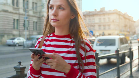 Young woman standing at old street and using smartphone at sunset. Communication Footage