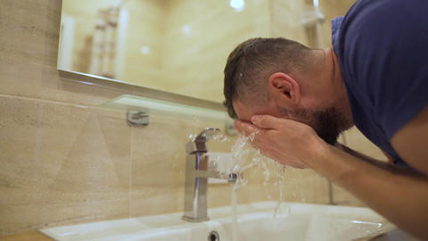 Morning hygiene. Man washes his face with clean water in the bathroom. Slow Live Action