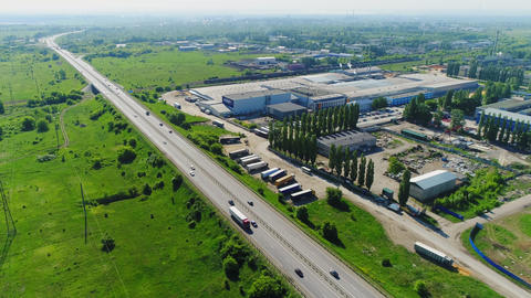 road with cars near industrial complex on sunny day aerial Footage