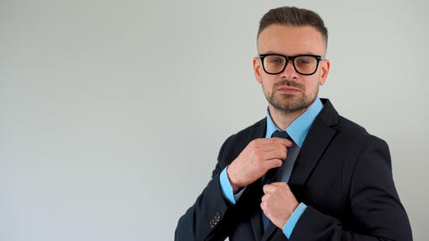 Portrait of a formally dressed bearded man with glasses straightens his tie and Archivo