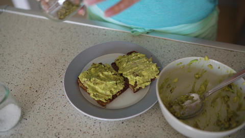 Woman cooking avocado toast, sprinkles it with salt and spices Footage