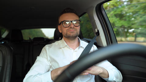 Bearded man in glasses and white shirt driving a car in sunny weather and uses Live Action