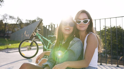 Portrait of two cheerful caucasian young women with long hair, fashion glasses Footage