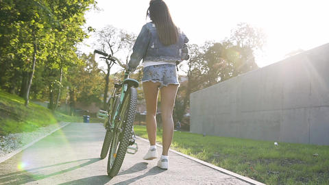 View from back of young woman walking on city streets with bicycle in summer day Footage