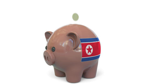 Putting money into piggy bank with flag of North Korea. Tax system system or Live Action