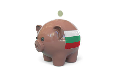 Putting money into piggy bank with flag of Bulgaria. Tax system system or Live Action