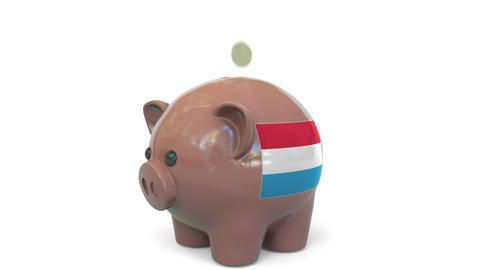 Putting money into piggy bank with flag of Luxembourg. Tax system system or Live Action