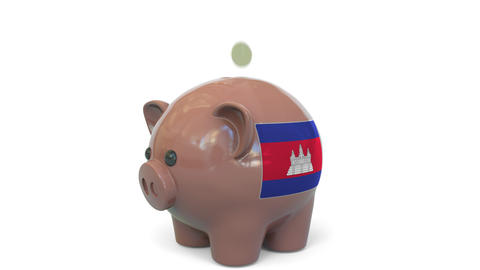 Putting money into piggy bank with flag of Cambodia. Tax system system or Live Action