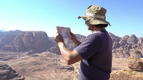 Man with map standing at the edge of mountains and looking around Footage