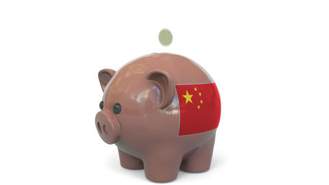 Putting money into piggy bank with flag of China. Tax system system or savings Live Action