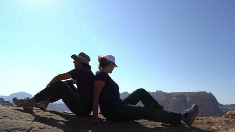 Couple of hikers sitting on the edge of mountains, love, friendship, partnership Live Action