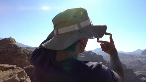 Man doing photo frame by his hand over beautiful mountain landscape Footage