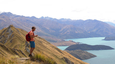 Travel Tourist Hiker Taking Landscape photo with phone on Mountain New Zealand Archivo