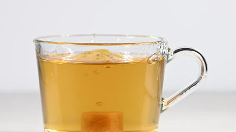 Throwing brown sugar cubes in cup of green tea Live Action