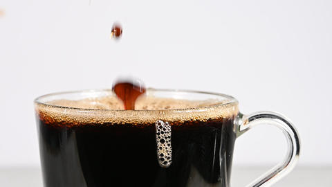 Throwing brown sugar cubes in cup of black coffee Live Action